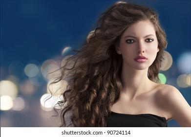 beauty fashion portrait of a very young cute brunette with long curly hair with hairstyle flying in the wind on city light bokeh