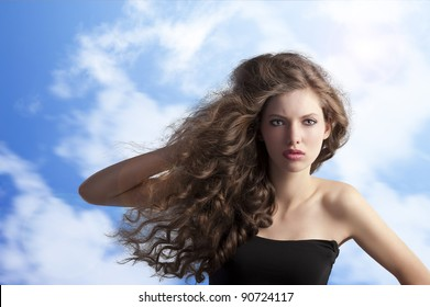 beauty fashion portrait of a very young cute brunette with long curly hair with hairstyle flying in the wind on sky background