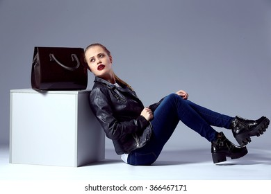 Beauty fashion portrait of Vogue style amazing young blond woman with bright make-up, black bag near cube in studio