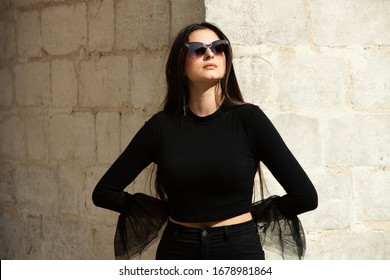 Beauty fashion portrait of young beautiful brunette girl with long black hair wearing sunglasses. Beauty Russian girl face with natural skin. European glamour. Pretty hipster girl in sunglasses.