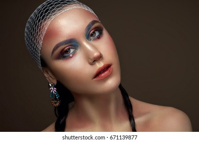 Beauty fashion portrait of young beautiful brunette girl with pigtails. Pearls on eyes. Art makeup
