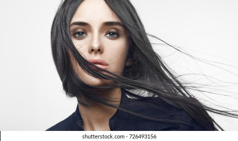 Beauty fashion portrait of young beautiful brunette girl with long black straight flying hair. Magnificent hair. Vogue style
