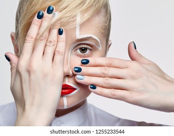 Beauty fashion portrait of a young woman on gray background. Female with an unusual creative makeup face painting. Girl with hands near face.