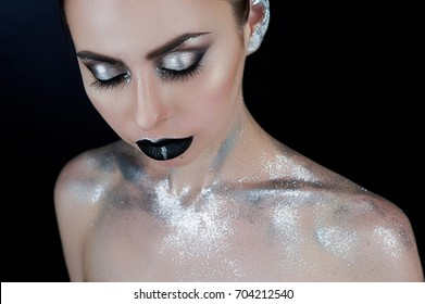Beauty, fashion portrait. Portrait of a young woman with silver glitter make-up, black lips, closed eyes over black background. Body paint, make-up project.