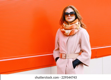 Beauty, fashion, shopping and people concept - pretty stylish woman in coat and sunglasses posing outdoors against colorful wall in the city