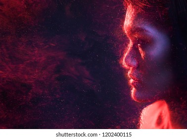 Beauty, fashion. Silhouette of woman in red sparks at night