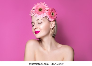 Beauty fashion spring spa girl portrait. Beautiful young woman on pink Gerber daisy wreath studio portrait. Holiday make-up and dreaming mood.