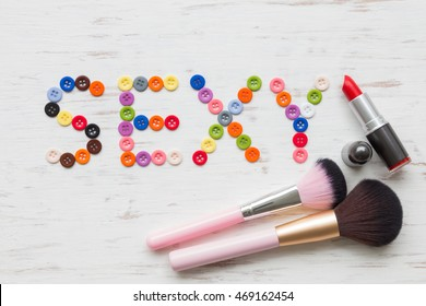 Beauty and fashion style concept with color buttons sexy word and set of cosmetics on white rustic wooden background