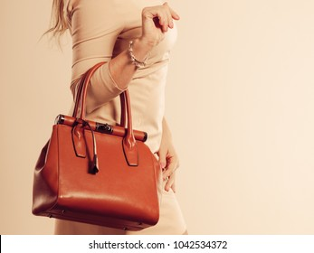 Beauty and fashion. Stylish fashionable woman wearing bright dress holding brown bag handbag, studio shot toned image