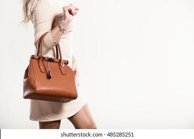 Beauty and fashion. Stylish fashionable woman wearing bright dress holding brown bag handbag, studio shot