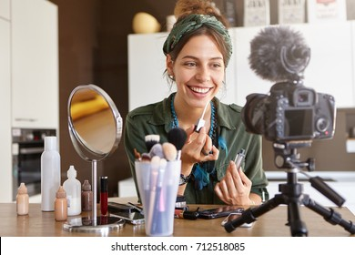 Beauty, fashion, technology, media and networking. Pretty girl vlogger sitting at dressing table surrounded with diverse cosmetics, looking at camera fixed on tripod while recording make up tutorial