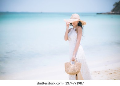 Beauty and Fashion theme of sexy women with white dress , sunhat and Knitting bag at beach