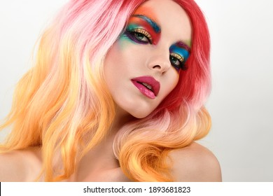 Beauty Fashion woman with Colorful Bright Art Makeup, Pink Dyed Hairstyle. Girl with blue eyes, stylish hair, make up. Beautiful model portrait, fashionable color trend creative make-up.