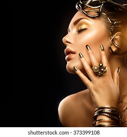 Beauty Fashion woman with Golden Makeup, accessories and nails. Girl Portrait with gold earrings, rings, bracelets and manicure closeup isolated on black background. Fashion art Hairstyle and make up