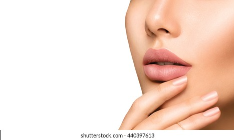 Beauty Fashion woman lips with natural Makeup and beige Nail polish. Matte lipstick and nails. Beauty girl face close up. Nude Colors. Sexy lips, Manicure, Make up. Isolated on a white background
