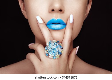Beauty Fashion woman lips with natural Makeup and white Nail polish. Gloss Blue Lipstick. Beauty girl face close up. Sexy Lips, Manicure, Make up. Ring with Precious Stones, Jewelry