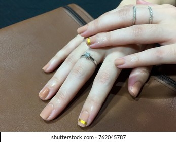Beauty Fashion woman nails with natural beige nail polish. Matte nails. Nude Colors. Manicure, Nail artist. Over brown background.