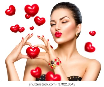 Beauty Fashion Woman showing red heart in her hand. Love concept, Valentine's Day. Beautiful model girl winking and kissing. Isolated on a white background