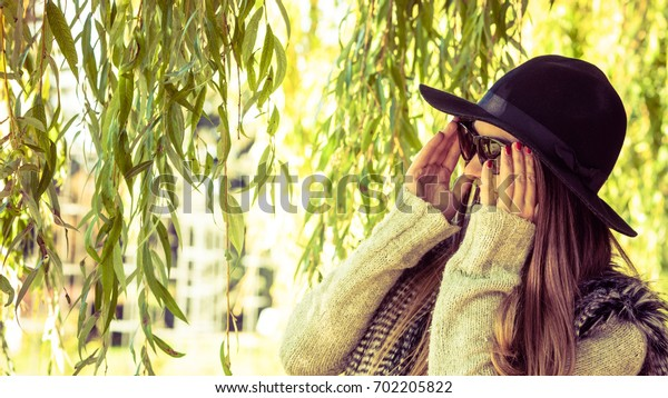 Beauty and fashion of women. Young attractive fashionable girl wearing stylish hat waistcoat and sunglasses. Pretty woman around leaves of willow tree.