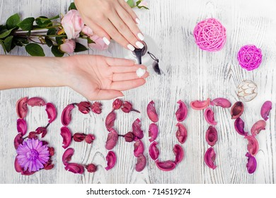 Beauty female hands cream for hands flowers on white wooden background isolation
