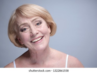 beauty female  happy lady  portrait toothy smile smiling studio shot woman old mature riffle  on gray background face skin teeth care blond