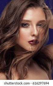 Beauty female model with beautiful make-up color and long hair. Brown hair, clean shiny skin, face of beauty. Glamorous portrait in studio