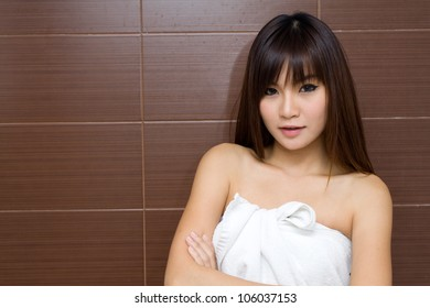 Beauty female portrait with a towel wrapped in the bathroom