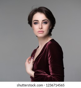 Beauty female portrait. Young attractive woman posing at studio over gray background. Beautiful model with perfect make-up dressed evening burgundy dress looking at camera.
