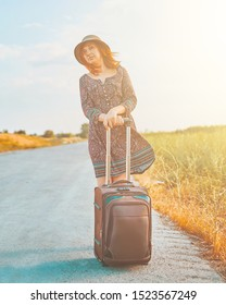 Beauty female tourist in summer dress and hat hitchhiking with suitcase on the road at fall. Cute woman stands next to the Luggage waiting for the bus. Hitchhiker concept