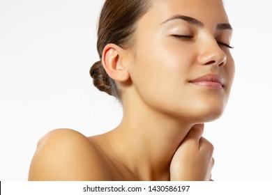 Schönheit weibliches Porträt von weiblichem Gesicht mit gesunder natürlicher Haut. Schönes gegerbtes Teenager-Mädchen mit langbraunem Haar und Blick auf die Kamera. Hübsch attraktive junge Frau, die sich im Studio posiert, einzeln auf Weiß