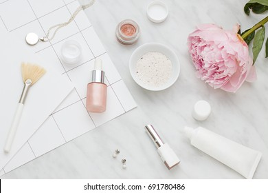 Beauty flat lay with cosmetic bottles and flower. Top view