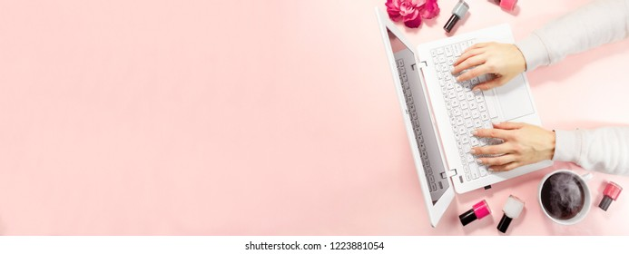 Beauty flat lay with a laptop and flowers. Woman's hands working on white laptop and a cup of coffee. Top view composition. long banner with copy space.