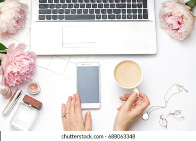 Beauty flat lay with a laptop and flowers. Woman's hands hold a phone and a cup of coffee. Top view composition.