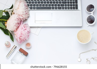 Beauty flat lay with a laptop and flowers.Top view composition. Copy space