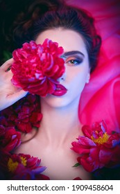 Beauty and flowers. Stunning brunette woman with bright make-up lying among peony flowers. Cosmetics, make-up. Perfumery.