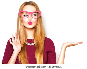 Beauty funny teenage girl with paper glasses on stick showing empty copy space on the open hand palm for text, white background. Happy girl presenting point. Proposing product. Advertisement gesture