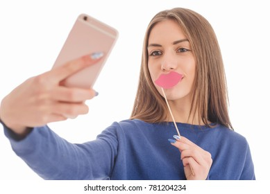 Beauty funny teenage girl with paper mouth on stick making selfie with her cellphone