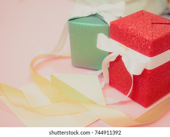 beauty gift box wrapping by red and green shiny paper with ribbon decoration for celebration christmas , birthday or new year put on pink pastel background