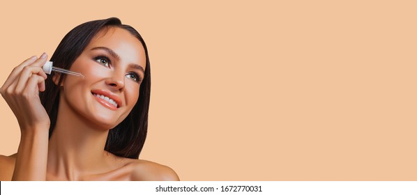Beauty girl applying serum on face with pipette. Happy beautiful girl with perfect clean healthy skin looking to the side. Pretty woman clean fresh skin. Expressive facial expressions. Cosmetology.