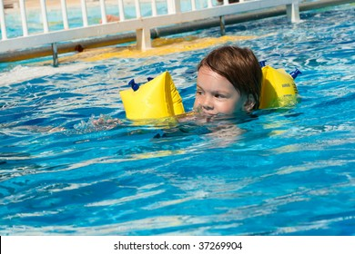 Beauty girl with armlet swimming in swimming pool with blue water.