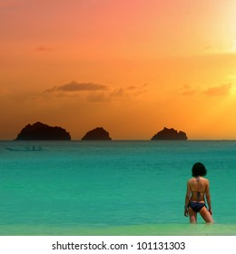 Beauty girl in bikini at the sea is standing knee-deep in water on sunset background.