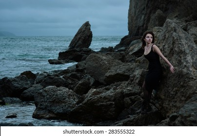 Beauty girl with black eyes in dramatic sea storm in black dress