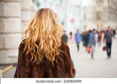 Beauty girl with blonde curly in fur coat walking autumn street. Healthy Wavy hair. Back view