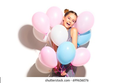 Beauty girl with colorful air balloons laughing, isolated on white background. Beautiful Happy Young woman on birthday holiday party. Joyful model having fun and celebrating with pastel color balloon