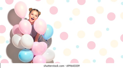 Beauty girl with colorful air balloons laughing isolated on white background. Beautiful Happy Young woman on birthday holiday party. Joyful model having fun and celebrating. Polka dots background.