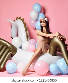 Beauty girl with colorful pastel air balloons laughing over pink background. Beautiful happy young woman on birthday holiday party having fun celebrating on unicorn pegasus float