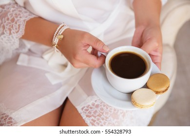 Beauty girl with cup of coffee and macaroon, bride's morning, cozy morning