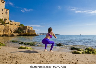 Beauty girl doing work outs in a desert beach