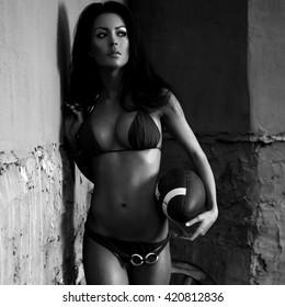 Beauty girl dressed bikini poses holding a ball. Black-white outdoor photo.