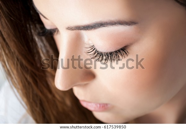 Beauty girl with extended silk eyelashes and eyes closed in a beauty studio, close up